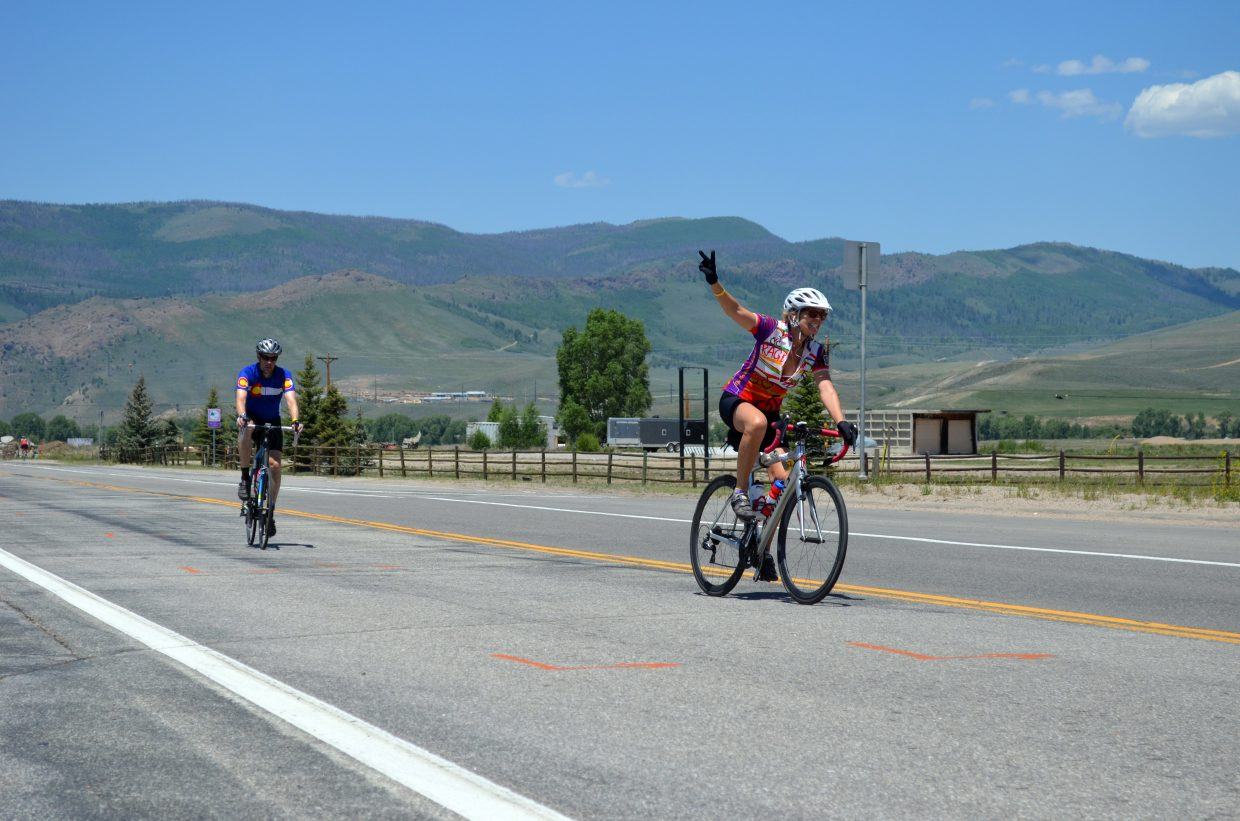 A rider happily offers a wave as she make the trek to Grand Lake on Wednesday during Ride the Rockies.
