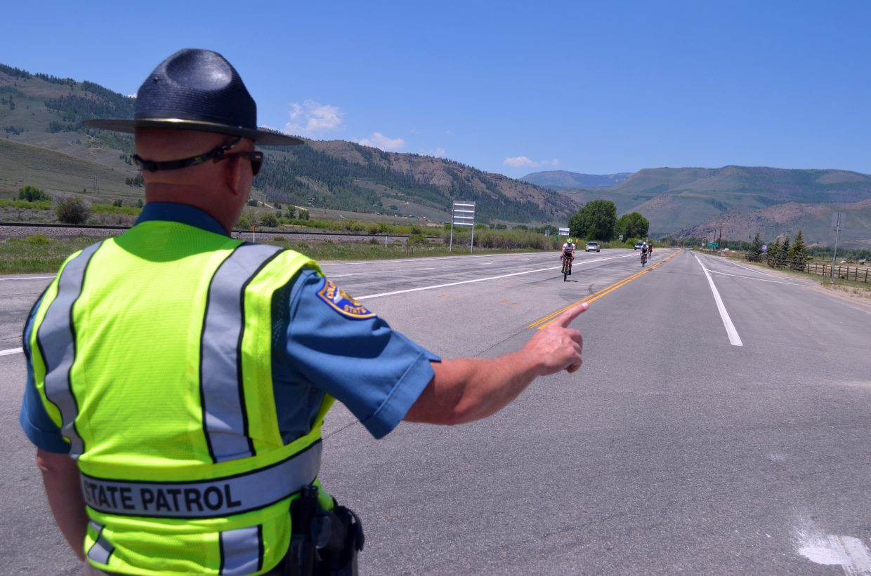 A state patrolman directs bicyclists as they approach the intersection of Highway 34 and 40 on their way to Grand Lake.