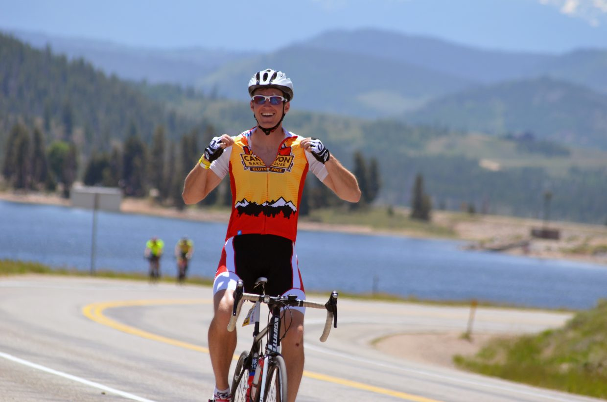 A rider joyously tugs on his racing outfit Wednesday as cyclists made their way up Highway 34 to Grand Lake during Ride the Rockies.