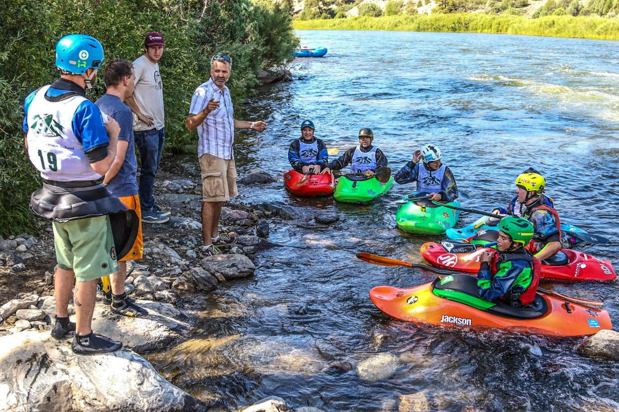 A group of kitted out kayakers rest along the banks of the Colorado listening to instructions.