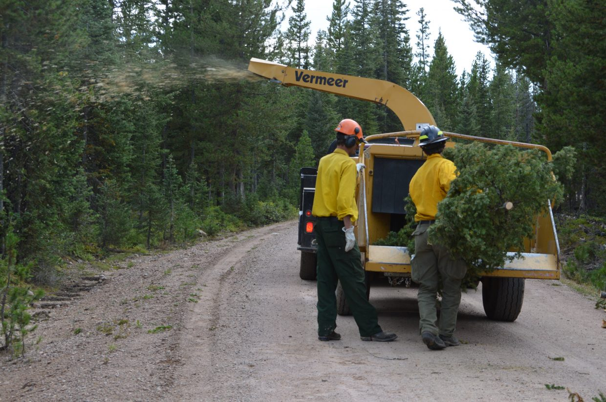 Crews hand load smaller trees and branches into the chipper. Chipping the materials helps remove the fire's fuel.