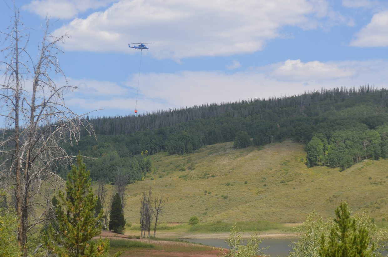 A KMAX helicopter carries 375 gallons of water to dump on a spot fire site.