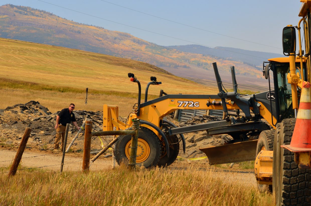 Lt. Dan Mayer of the Grand County Sheriff's Office opens up a closed road for road graders on Friday, Sept. 14.