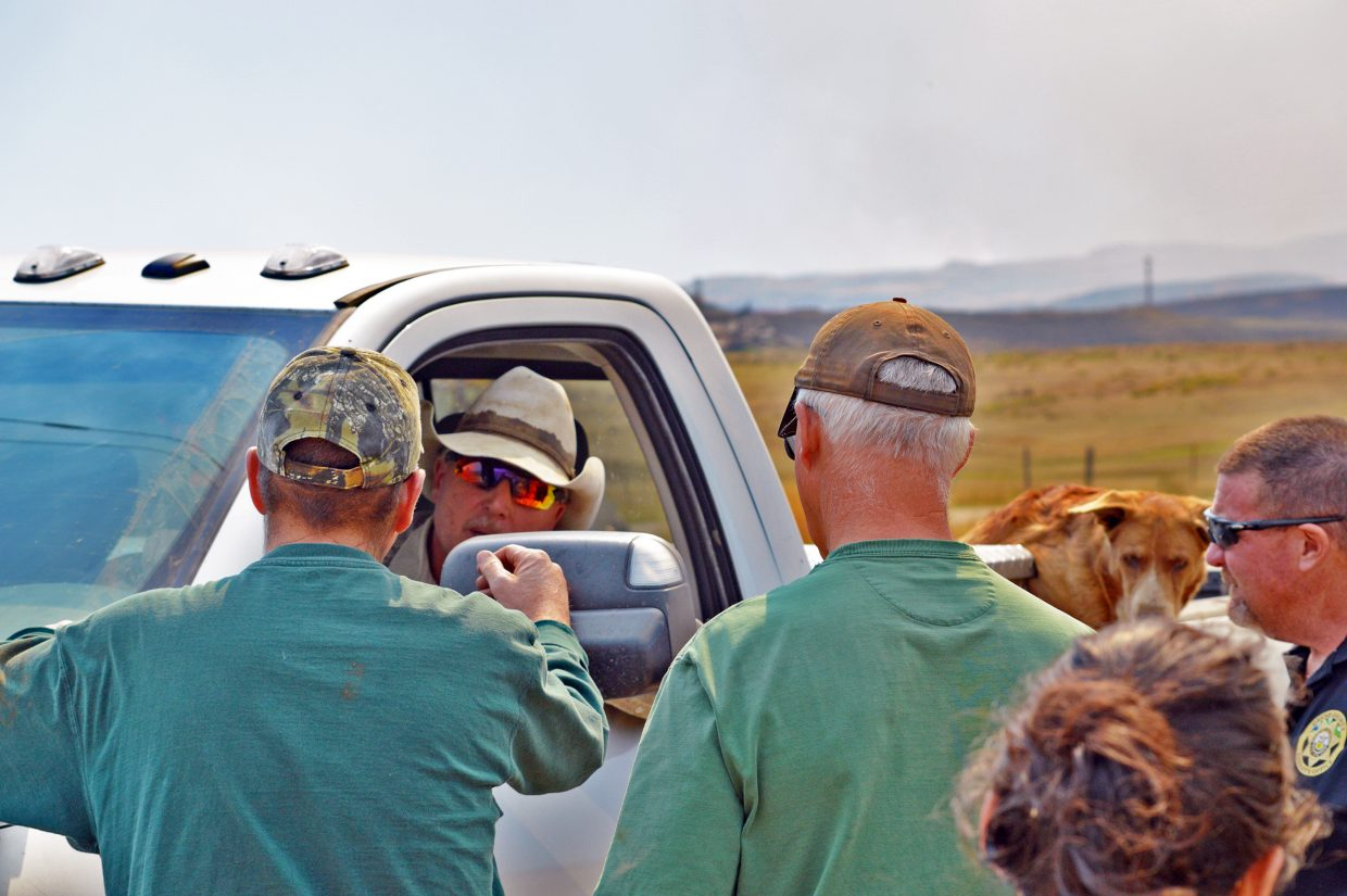 Rich Sherman sits in his truck while speaking to the road graders and Lt. Dan Mayer with the Grand County Sheriff's Office on Friday, with the smoke from the Silver Creek Fire ongoing in the background.