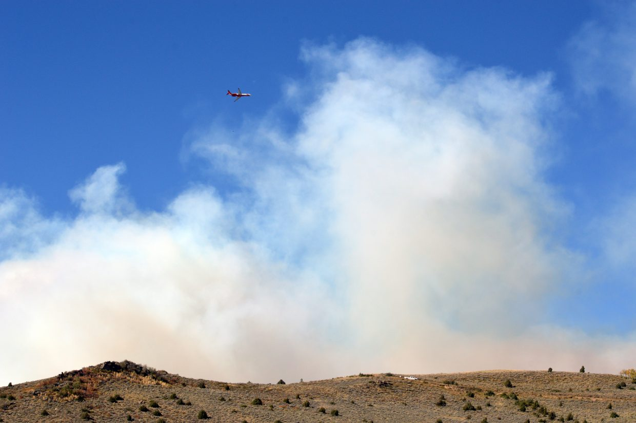 A 737 flies over the Old Park neighborhood, circling the Silver Creek Fire on Friday.