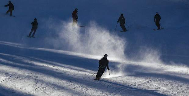 Skiers and snowboarders make some of the first runs of the season on opening day at Arapahoe Basin Ski Area on Friday.