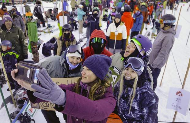 Kelly Spence, of Breckenridge, takes a photo with a group set to ride the first chair of the season on opening day at Arapahoe Basin Ski Area on Friday.