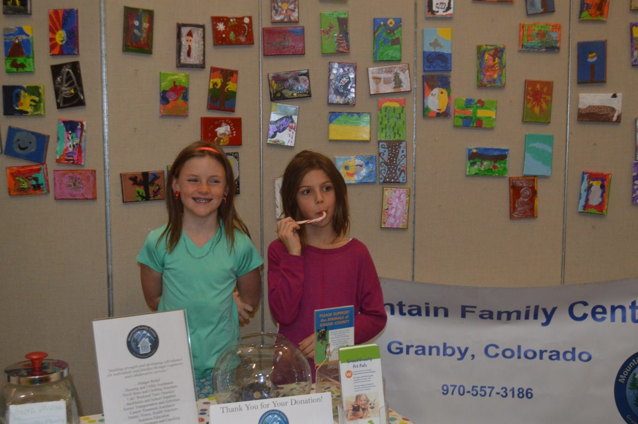 Two students who participated in the Art For a Cause program stand at the booth selling their work.