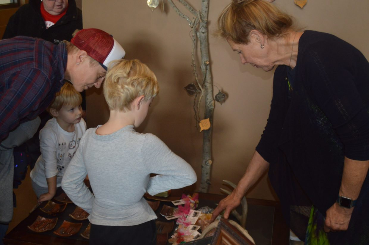 Donna Line, artisan at Buffalo Valley Soaps, shows some customers her crystals and handmade soaps.