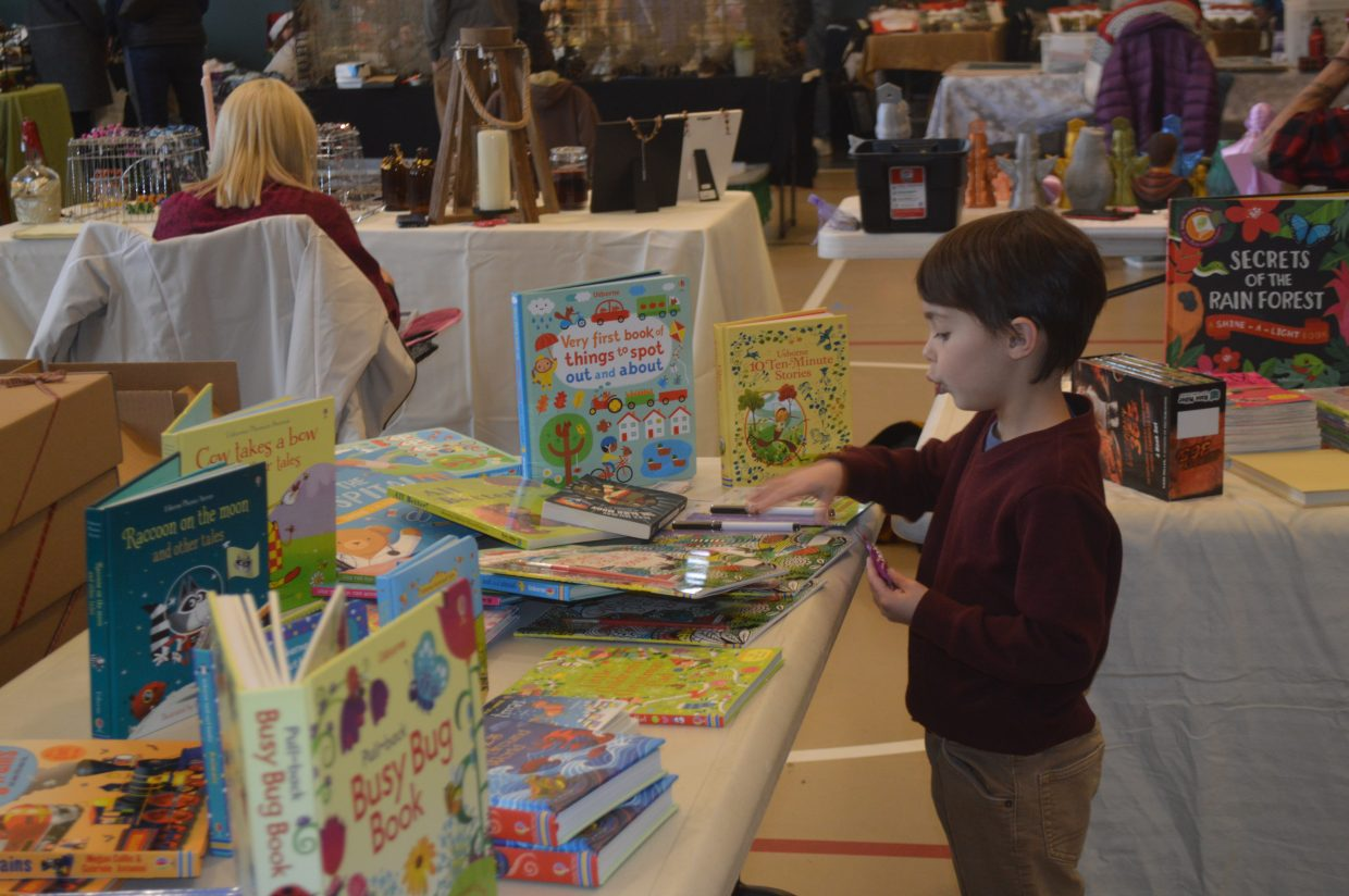 A young boy explores a children's book booth. All of the booths at the craft fair featured holiday gift items.