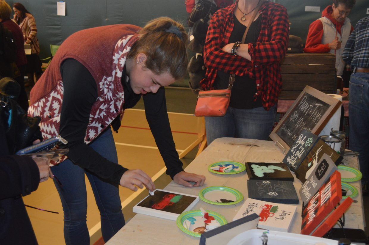 Sydney Ritschard, from Kremmling, paints at a do-it-yourself station for wooden holiday signs.