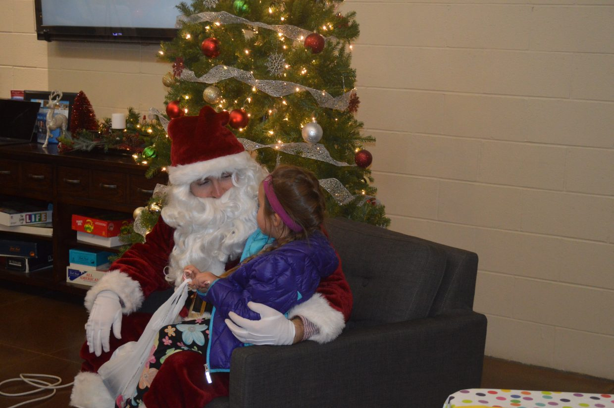 Eliana, 5 from Granby, sits on Santa's lap at the Fraser Valley Holiday Craft Fair on Saturday.