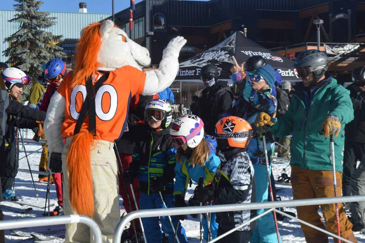 Broncos' mascot Miles high fives some skiers while they wait in line for the Arrow lift.