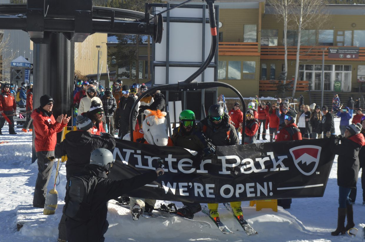 The first chair breaks through the banner on opening day.