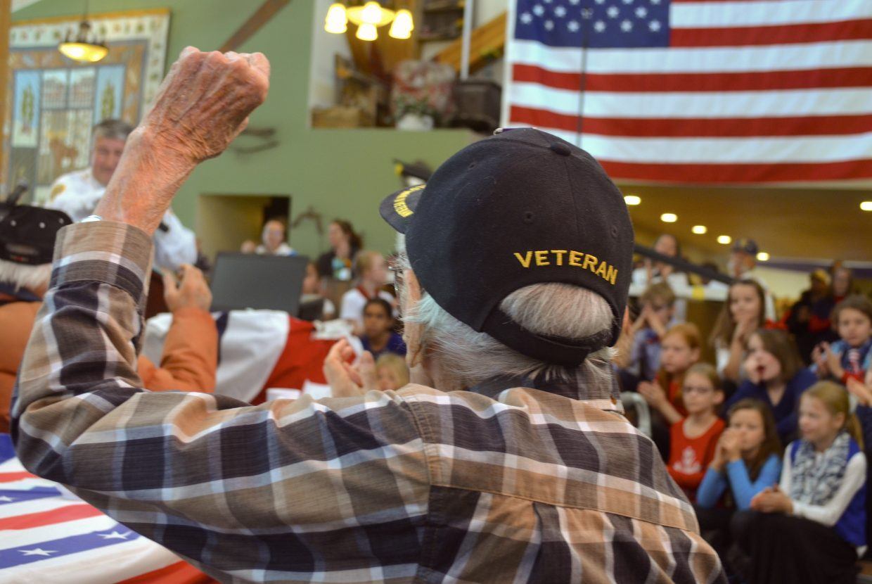 10) JR Rauenbuehler, one of Grand County's World War II veterans, raises his arm during the roll call portion of Monday's Veterans Day event.