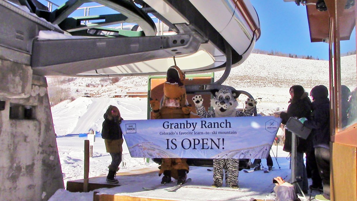 G-Rex, donning skis, and Ski Granby Ranch mascot Snowball break through the ceremonial opening day banner Friday morning at Ski Granby Ranch.