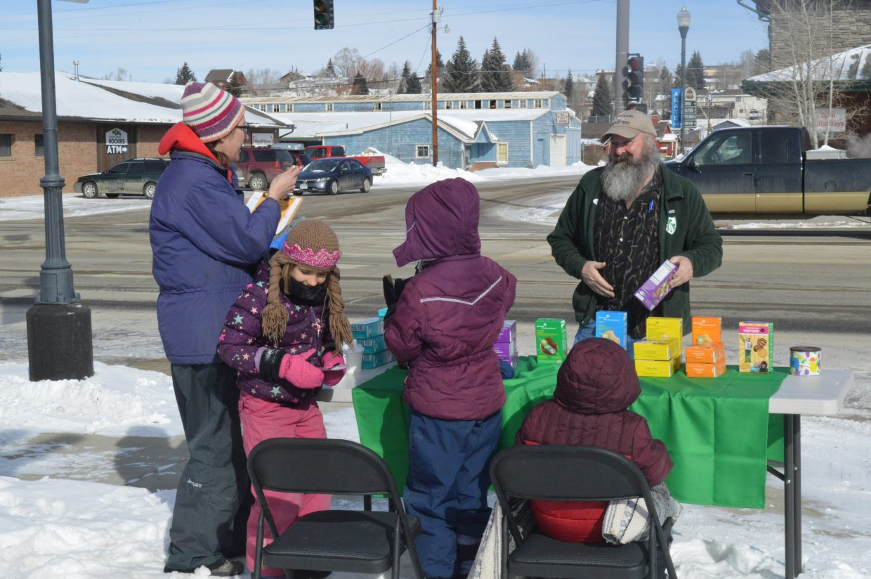 A local buys a box of Samoas from Leah and Annabelle, while mom Alicia Scott keeps track of the sales.