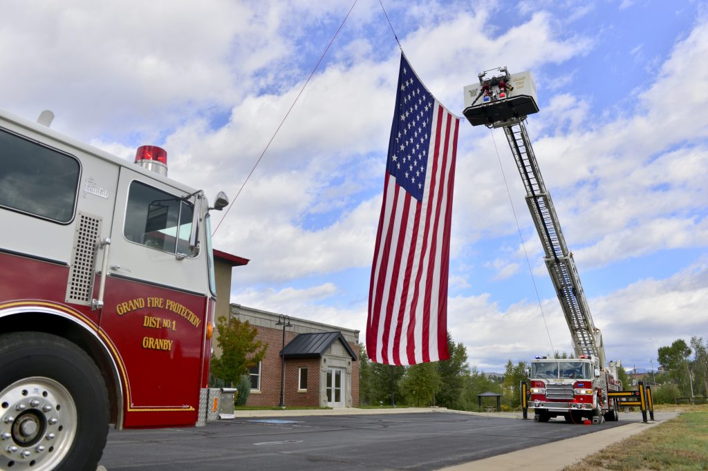 A large American flag hangs from two fire trucks at the Grand Fire Protection District on Wednesday.