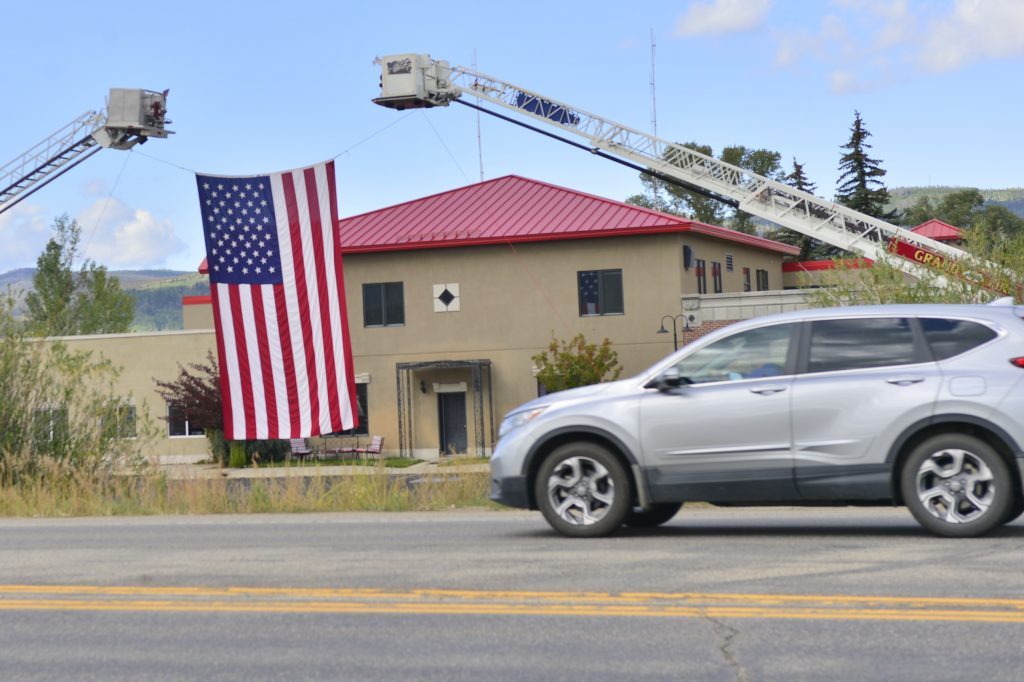 Drivers pass an American flag in front of the Grand Fire Protection District in this file photo.
