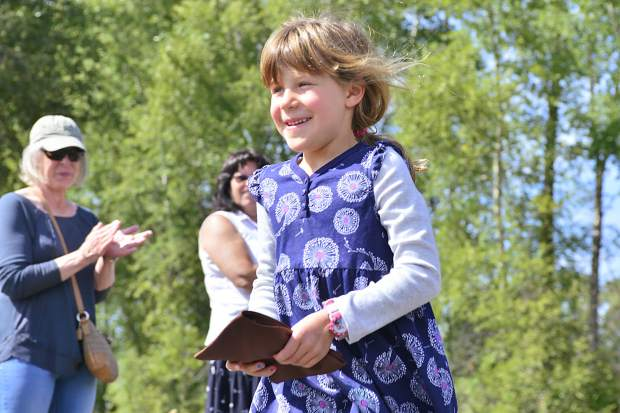 Girl Scout Naiomi Glick is all smiles after crossing the bridge Sunday in Granby.