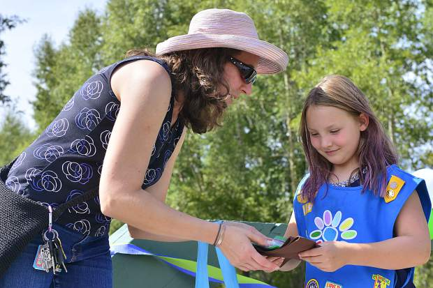 Troop leader Alicia Scott gives Girl Scout Chloe Fanning her new sash on Sunday during a Girl Scout bridging ceremony in Granby.