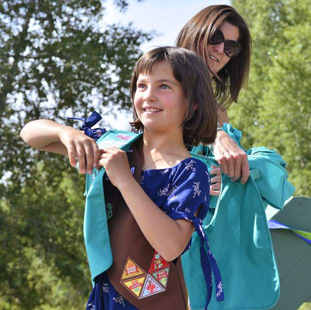 Molly Turk helps Alivia Martin put on a new green vest during a Girl Scouts bridging ceremony Sunday in Granby.