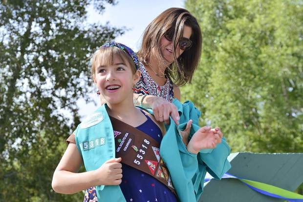Molly Turk helps Elana Holden put on her new green vest during Sunday's bridging ceremony in Granby.