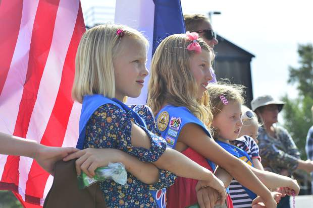 Sloane Bishop, Laila Waldow and Sadie Stoltz join hands during a bridging ceremony Sunday in Granby.