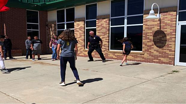 Local officers visit with students and even play some games with them outside.