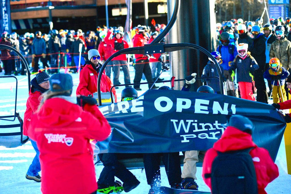 The first chair lift breaks through a banner signifying the opening of Winter Park Resort on Saturday.
