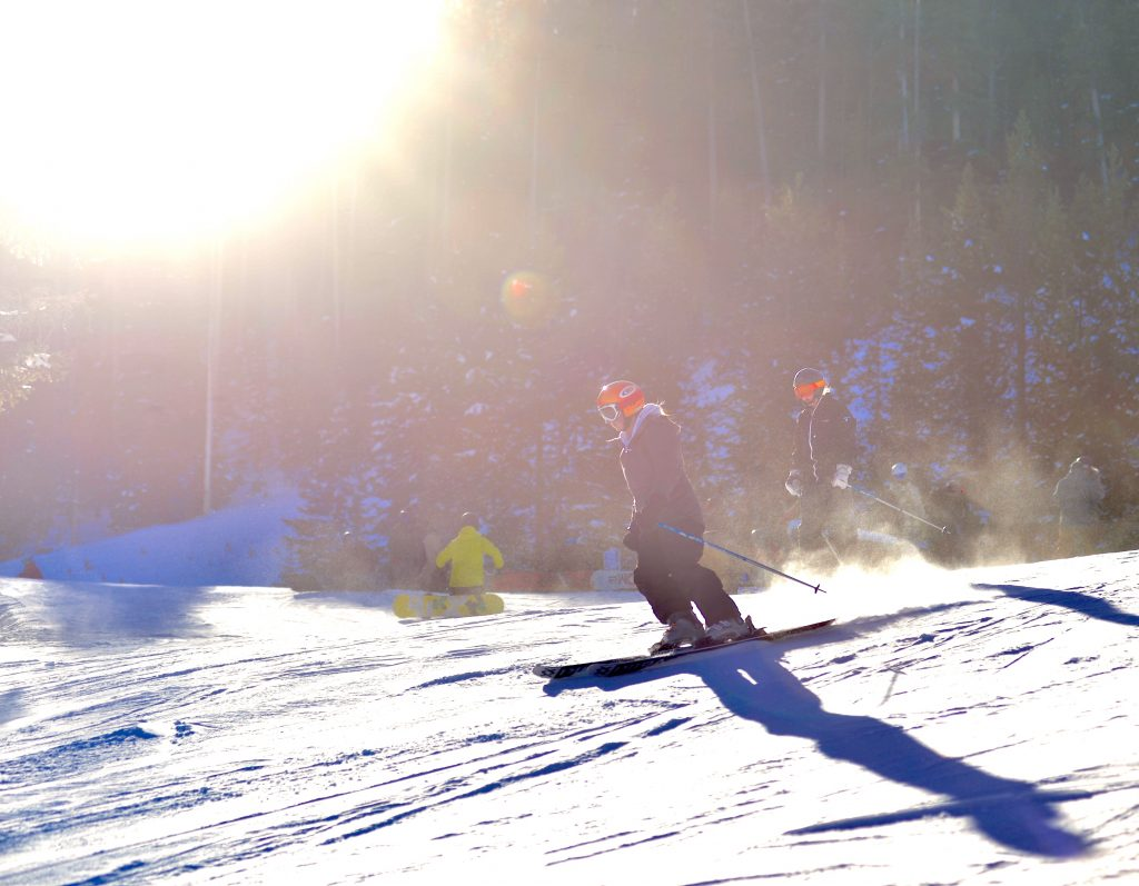 The sun peeks over the mountain as skiers and snowboarders take their first runs of the 2019-20 ski season at Winter Park Resort on Saturday.