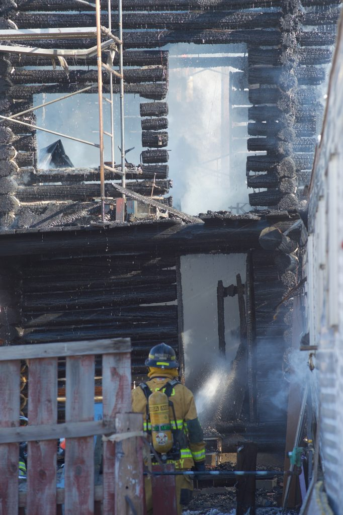 Firefighters work to suppress a house fire Friday afternoon in Tabernash. No one was hurt by the fire, but the log cabin structure was destroyed.