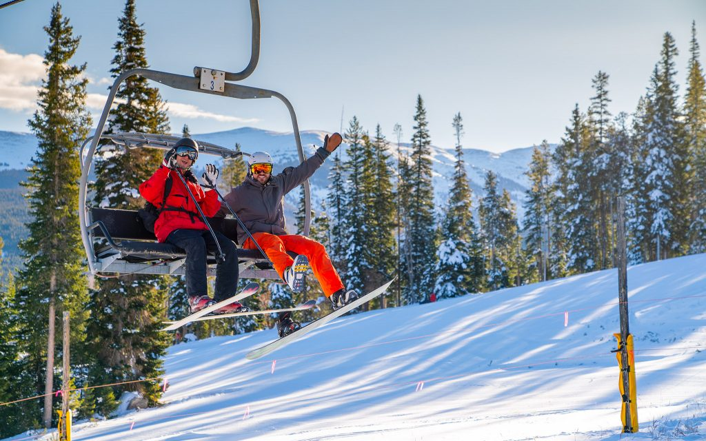 Skiers wave from a chair lift on Winter Park's opening day Saturday.