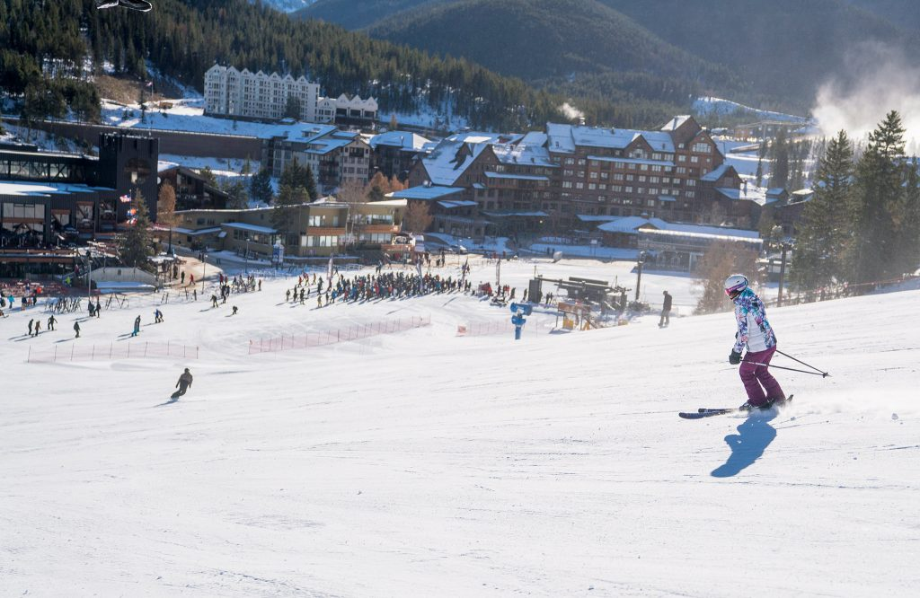 A skier goes down the slope as others wait in the background for their first run Saturday at Winter Park.