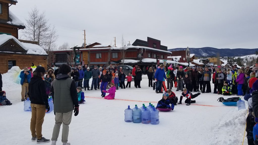 "Children and adults enjoy a little ""winter bowling"" during the winter carnival in downtown Grand Lake."