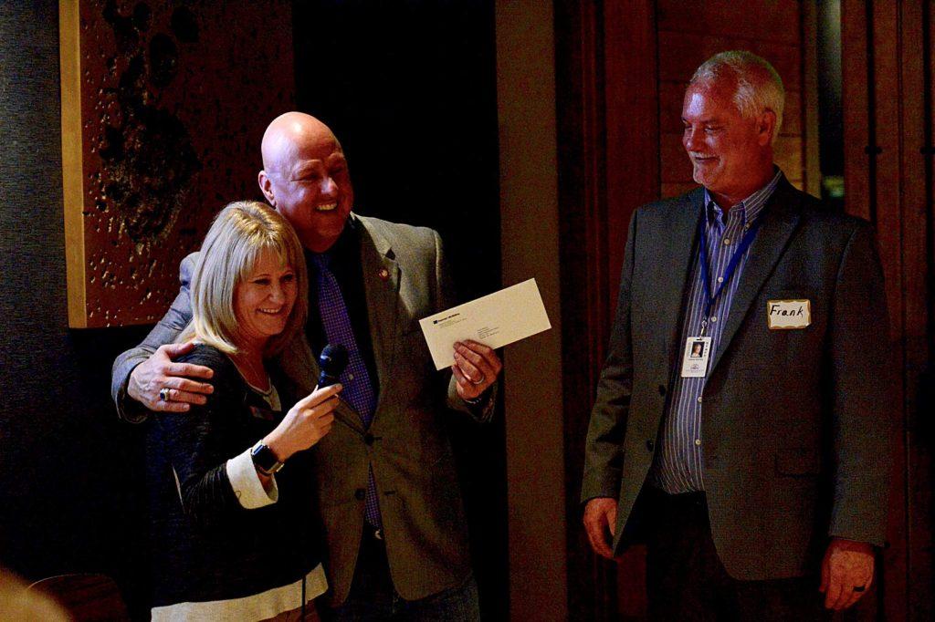 In this January file photo, West Grand Superintendent Darrin Peppard gives Tara Hosick a hug after she presented him and East Grand Superintendent Frank Reeves, right, a donation to support the schools' Homegrown Talent Initiative.