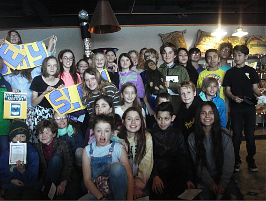 Fifth graders pose after performing their original poems during a poetry slam Monday at the Rocky Mountain Roastery.