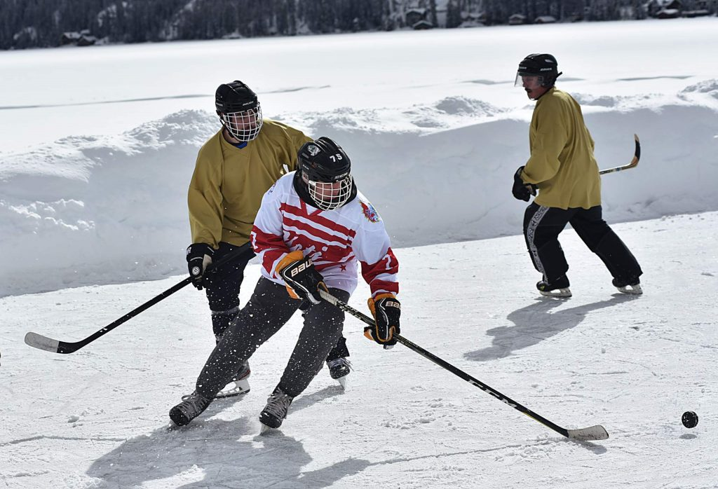Hockey players skate across a rink for the third annual Pond Hockey Classic on Saturday in Grand Lake. The event brought teams from across the state to participate in the new tradition.