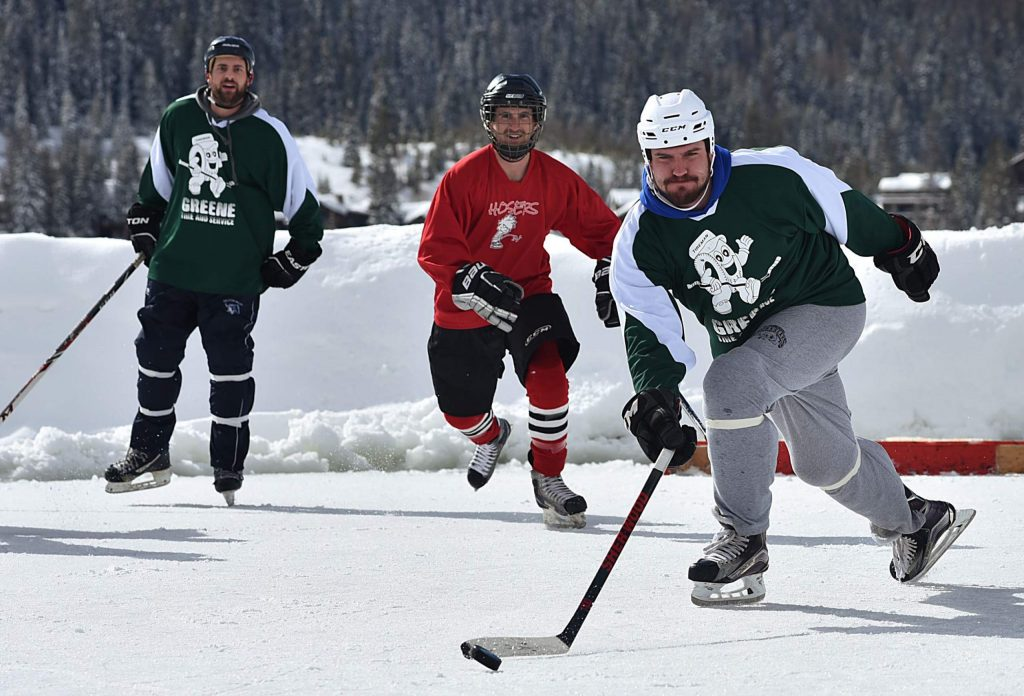 Hockey players persue a puck during a game at the Pond Hockey Classic on Saturday in Grand Lake. The third annual tournament faced three feet of snow that organizers and volunteers spent the proceeding days clearing.