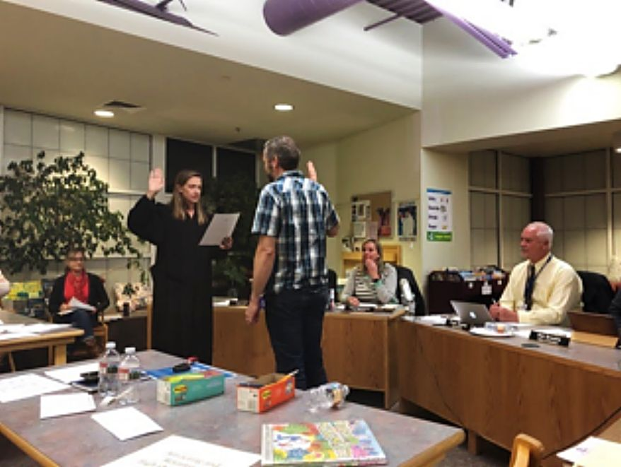 Shaul Hagen is sworn in as a new member of the East Grand School Board by Judge Mary Hoak at a board meeting in Fraser on Feb. 18.