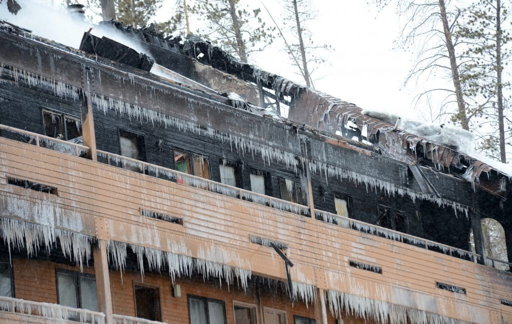 Ice hangs off the burned out Braidwood Condominiums building Monday in Winter Park.