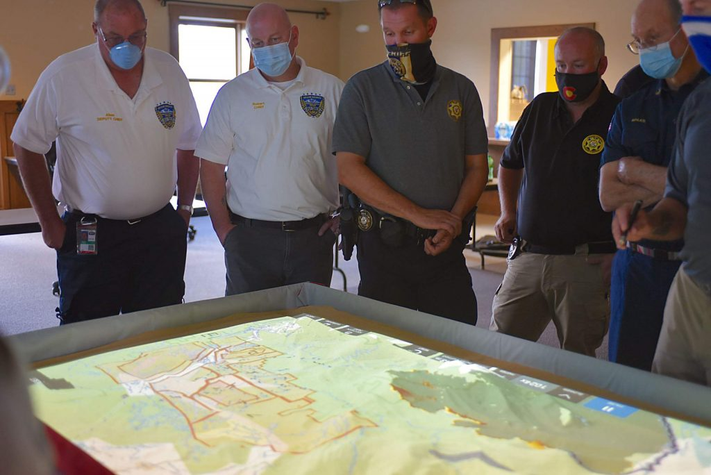 Deputy Chief of Grand County EMS Allan Pulliam, Chief of EMS Robert Good, Undersheriff Wayne Schafer and Sheriff Brett Schroetlin evaluate evacuation zones and fire behavior simulated by a SimTable on Wednesday at Grand Fire Station in Granby.