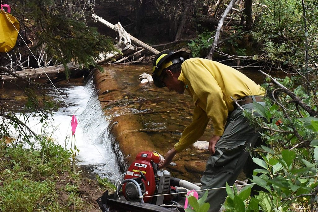 A firefighter turns off one of two pumps syphoning water from the creek to the 1,500 gallon pools in the Fraser Experimental Forest. People are working to protect valuable equipement and research in the area against the Williams Fork Fire.