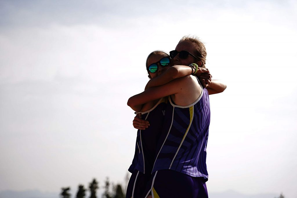 West Grand's Allura Luna and Samantha Westfahl hug after finishing the 3.1 mile course Saturday at Snow Mountain Ranch. Luna recorded the top finish for the Mustangs in the race by taking second.