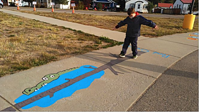 """A student at Granby Elementary student takes a stroll down the new """"sensory sidewalk"""" around the bus loop at the school."""